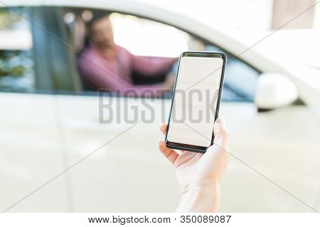 Cropped Hand Of Mid Adult Woman Using Mobile Phone With Blank Screen Against Car