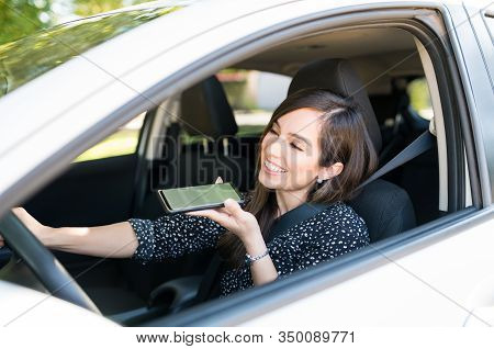Smiling Mid Adult Woman Talking On Smartphone While Sitting In Car