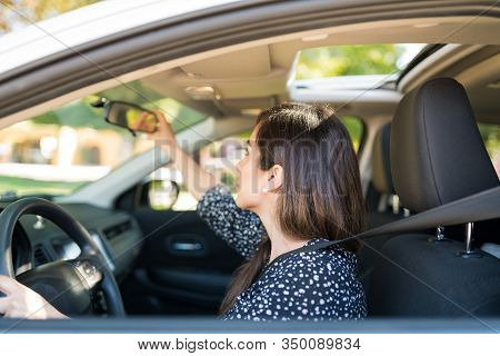 Mid Adult Latin Woman Adjusting Rearview Mirror In Car