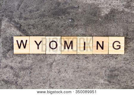 Wyoming Word Written On Wood Block, On Gray Concrete Background. Top View.
