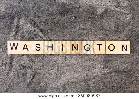 Washington Word Written On Wood Block, On Gray Concrete Background. Top View.