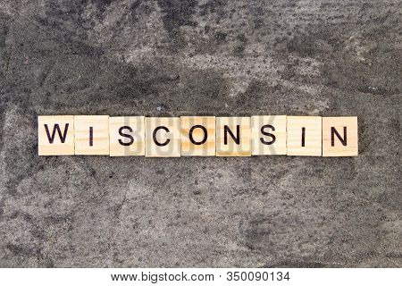 Wisconsin Word Written On Wood Block, On Gray Concrete Background. Top View.