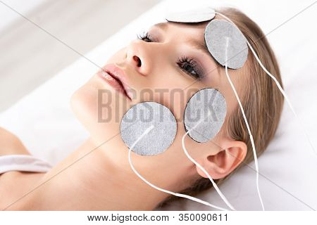 Attractive Woman Lying On Massage Couch During Facial Electrotherapy In Clinic
