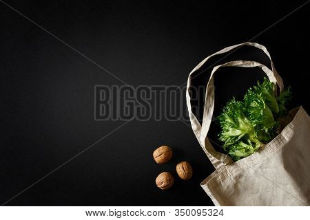 Walnuts, Lettuce Greens And A Grocery Canvas Bag On A Black Background.