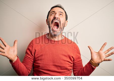 Middle age hoary man wearing casual orange sweater standing over isolated white background crazy and mad shouting and yelling with aggressive expression and arms raised. Frustration concept.