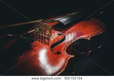 An Old Violin Lies On A Table Against A Dark Background.