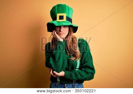 Beautiful brunette woman wearing green hat with clover celebrating saint patricks day thinking looking tired and bored with depression problems with crossed arms.