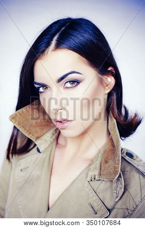 Attractive Girl In Coat With Perfect Skin. Makeup, Smooth Skin. Beauty Woman In Studio On Gray Backg