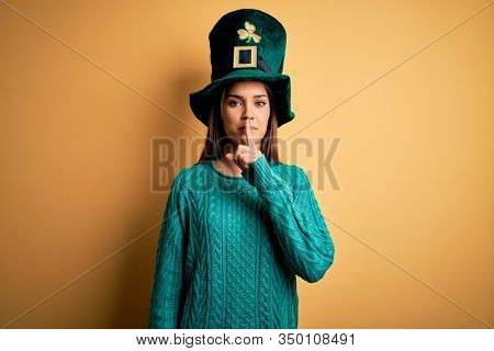 Young beautiful brunette woman wearing green hat with clover celebrating saint patricks day asking to be quiet with finger on lips. Silence and secret concept.