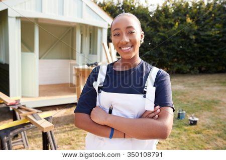 Portrait Of Female Carpenter Building Outdoor Summerhouse In Garden