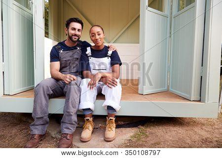 Portrait Of Couple Taking A Break From Building Outdoor Summerhouse In Garden