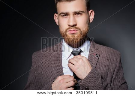 Studio Portrait Of A Young Bearded Handsome Guy Of Twenty-five Years Old, In An Official Suit, Tight