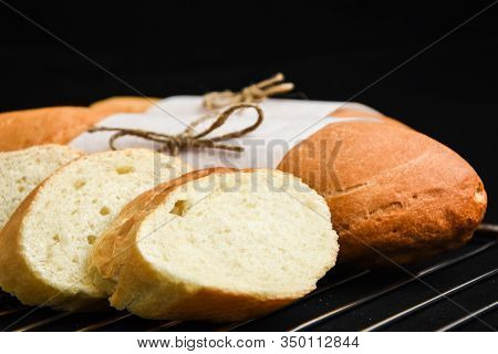Sliced French Baguette With Crumbs On Dark Background, French Homemade Baguette Bread. Wheat Baguett