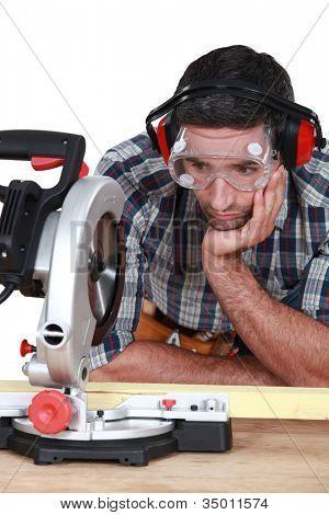 A man staring at a circular saw.