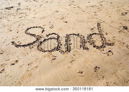 The Word Sand Written In Sand On The Beach