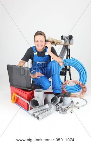 Female plumber knelt down by equipment