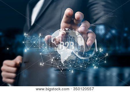 Global Business To Business Concept. Businessman Hand Reaches For The Planet With The Inscription B2