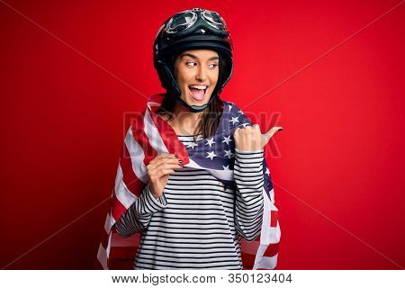 Young beautiful patriotic motorcyclist woman wearing moto helmet and united states flag pointing and showing with thumb up to the side with happy face smiling