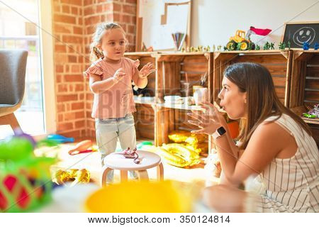 Beautiful teacher and blond student toddler girl acting and doing gesture like dinosaurs at kindergarten