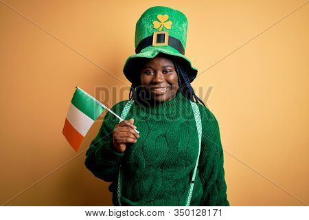 Plus size african american woman wearing green hat holding irish flag on saint patricks day with a happy face standing and smiling with a confident smile showing teeth