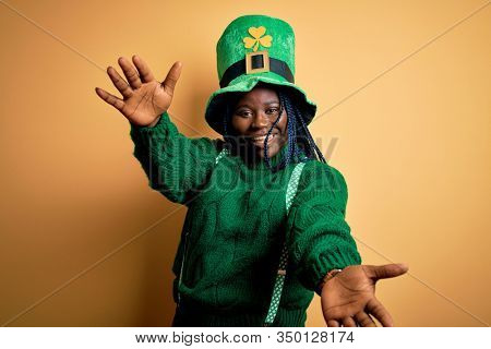 Plus size african american woman with braids wearing green hat with clover on st patricks day looking at the camera smiling with open arms for hug. Cheerful expression embracing happiness.