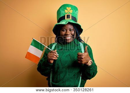 Plus size african american woman wearing green hat holding irish flag on saint patricks day happy with big smile doing ok sign, thumb up with fingers, excellent sign