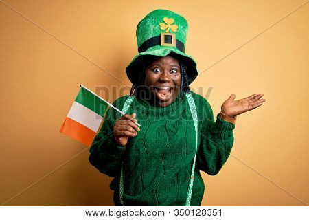 Plus size african american woman wearing green hat holding irish flag on saint patricks day very happy and excited, winner expression celebrating victory screaming with big smile and raised hands