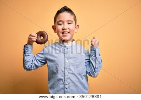 Young little boy kid eating unhealthy chocolate doughnut over isolated yellow background screaming proud and celebrating victory and success very excited, cheering emotion