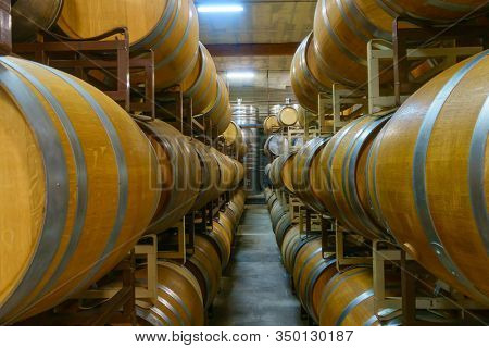 Interior of contemporary winery cellar with rows of stacked wooden barrels