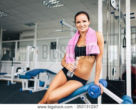 Front View Of Attractive Sporty Lady With Perfect Body Holding Bottle Of Water. Beautiful Athletic W