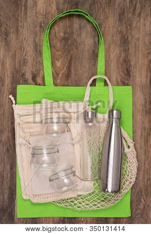 Zero waste eco friendly reusable objects such as reusable linen shopping bags, glass jars and bottles, top view on wooden background