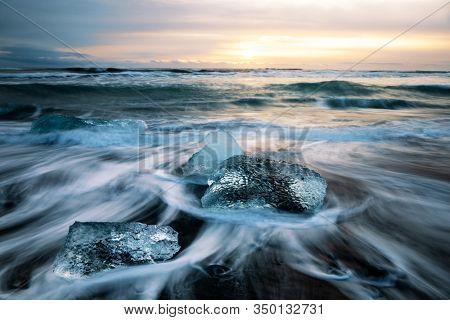 Sunrise on Diamond Beach, Iceland. The black volcanic sands are littered with chucks of glacial ice that have broken from the nearly glacier lagoon and drifted out towards the sea.