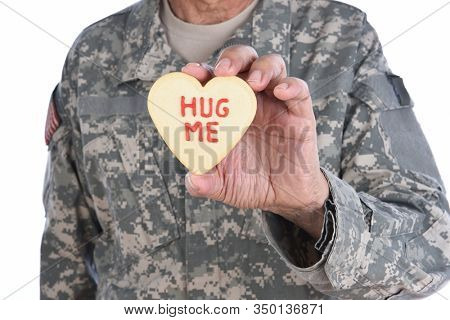 Closeup of a soldier holding a Heart Shaped Valentines Day cookie with the words Hug Me written in red icing.