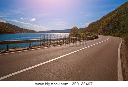 Asphalt Road Along The Sea Bay And Mountains Against The Blue Sky, Europe, Montenegro, Kotor