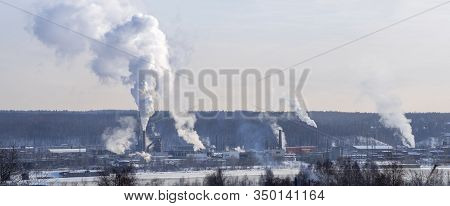 Factory Pipes Stand Along The Riverbank. Thick Smoke Rises From The Chimney-stalk. Behind The Chimne