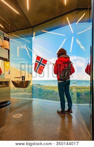 Tourist Woman With Norwegian Flag Enjoying Sea Coast View From Inside Of Mirrored Toilet Bukkekjerka