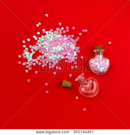 Two Heart Shape Bottles, Empty And Full Of Pink Confetti On Red Background. Love Potion Concept. Bre