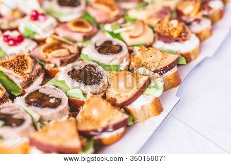 Close Up Of Crostini With Meat, Fruits, Vegetables And Cheese On Table.