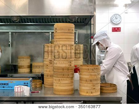 Chefs Cooking Chinese Dumplings By The Traditional Bamboo Steamers In A Restaurant. Dim Sum Chefs Wo