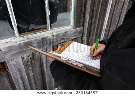 Home Inspector Taking Notes On A Notebook During An Inspection. Close Up On His Hands And The Pen As