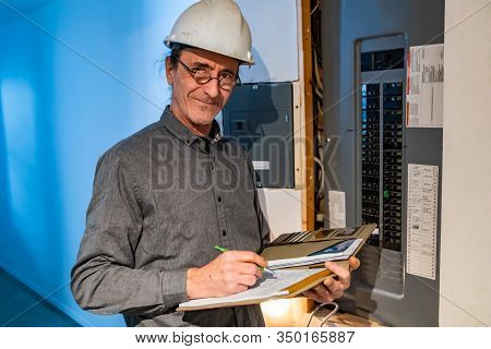 Home Inspector In Front Of Electric Distribution Board During An Inspection, A Caucasian Man Wearing