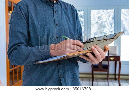 Inspector Holding A Notebook In His Hand. Close-up Of Mans Hands Taking Notes While Standing Indoor