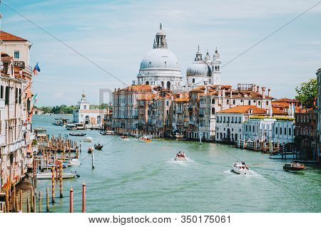 Venice, Italy. Daily Boat And Tourist Hectic On Grand Canal And Basilica Santa Maria Della Salute