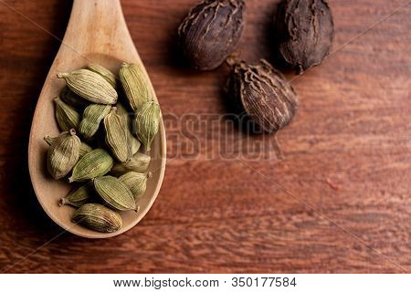 Close-up Of Dried Cardamom Pods In Spoon With Nutmeg On Wooden Background, Asia Spice For Cooking