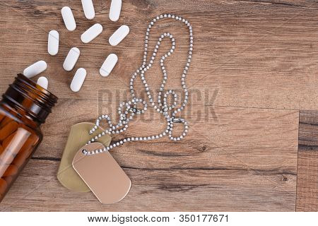 Military and Veterans Health Care Concept. Dog tags and pills on a wood background with copy space.