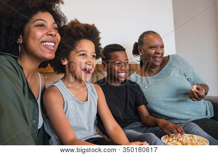 Portrait Of African American Grandmother, Mother And Children Watching A Movie And Eating Popcorn Wh