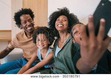 Portrait Of African American Family Taking A Selfie Together With Mobile Phone At Home. Family And L