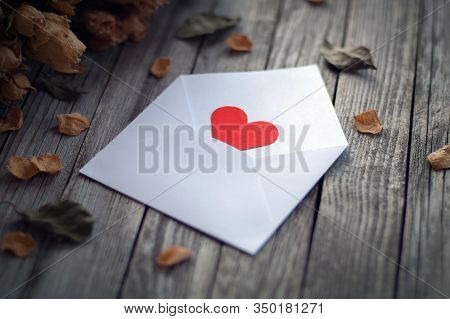 Open Envelope With Single Red Paper Heart Framed By Dry Roses On Wooden Table, Love Confession On Va