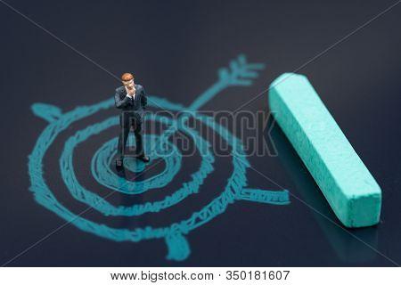 Miniature Businessman Standing On Chalk Drawing Bullseye Target With Pastel Green Chalk On Blackboar