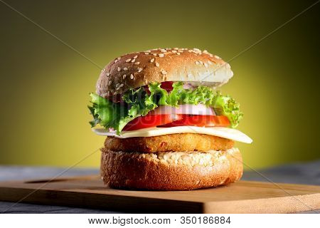 Fast Food - Burger On A Wooden Board And Yellow Background